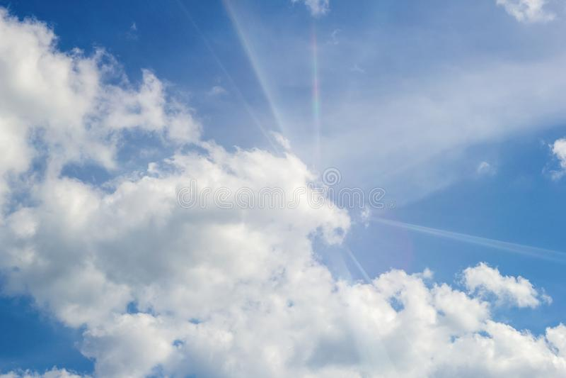 Beau ciel lumineux bleu, cumulus blancs et rayons du soleil photographie stock