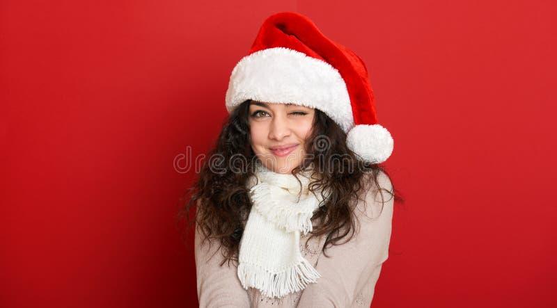 Beau clin d'oeil de jeune femme, portrait dans le chapeau d'aide de Santa et pose sur le rouge photos stock