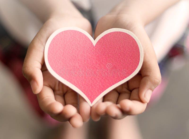 Beau coeur mis sur des mains de fille photos stock