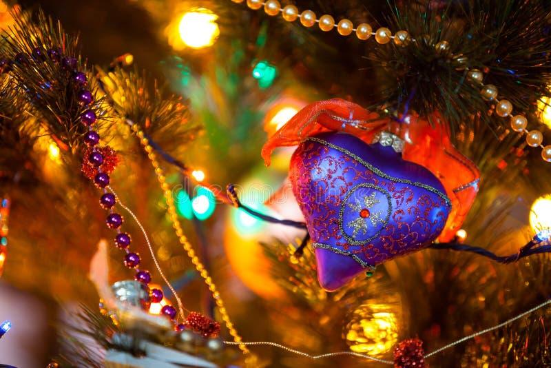 Beau coeur pourpre bleu accrochant sur le plan rapproché d'arbre de Noël photos stock