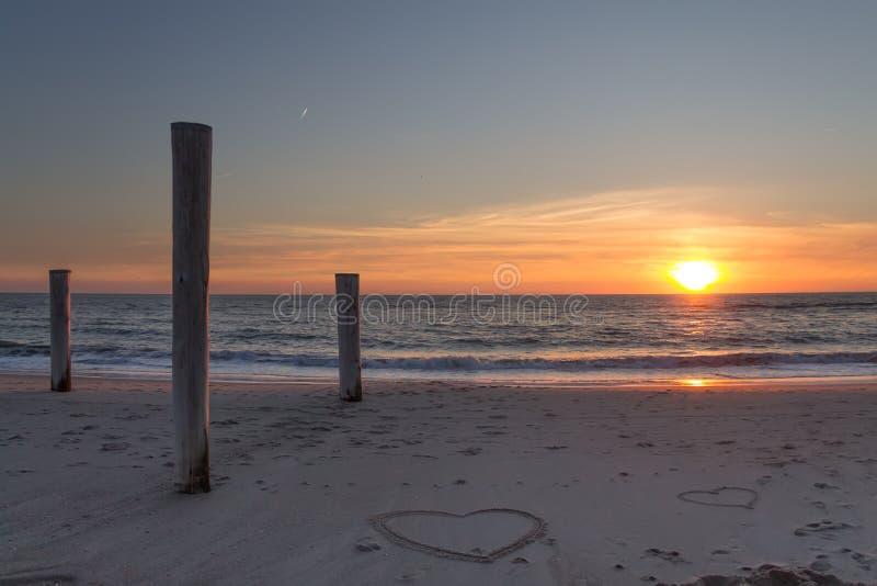 Beau coucher du soleil à la plage avec les piles et les dessins en bois de coeurs dans le sable photo libre de droits