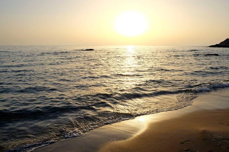Beau coucher du soleil au-dessus de la mer et des roches photo stock