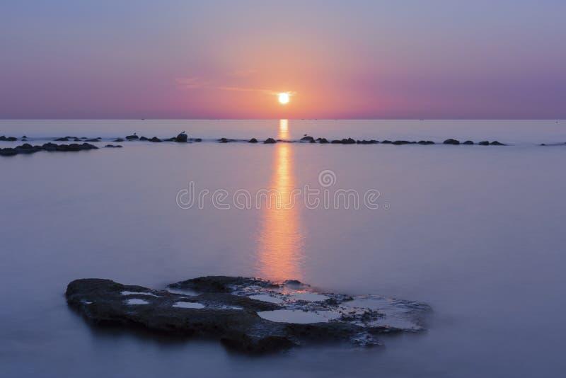 Beau coucher du soleil au-dessus de mer avec la r?flexion dans l'eau, nuages majestueux dans le ciel photo libre de droits