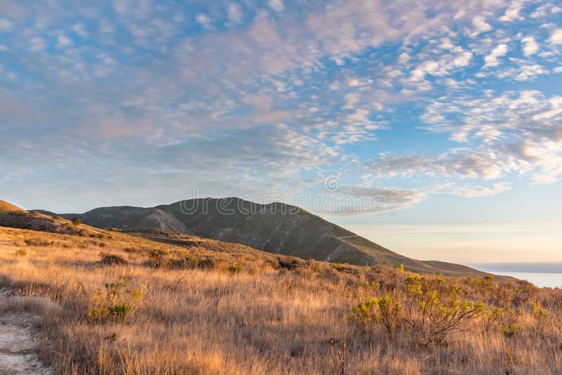 Beau coucher du soleil au-dessus des champs d'or avec la montagne photo stock