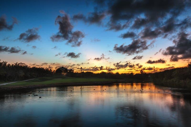 Beau coucher du soleil au-dessus du lac près du terrain de golf dans un tropica image libre de droits