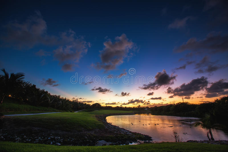 Beau coucher du soleil au-dessus du lac près du terrain de golf dans un tropica images libres de droits
