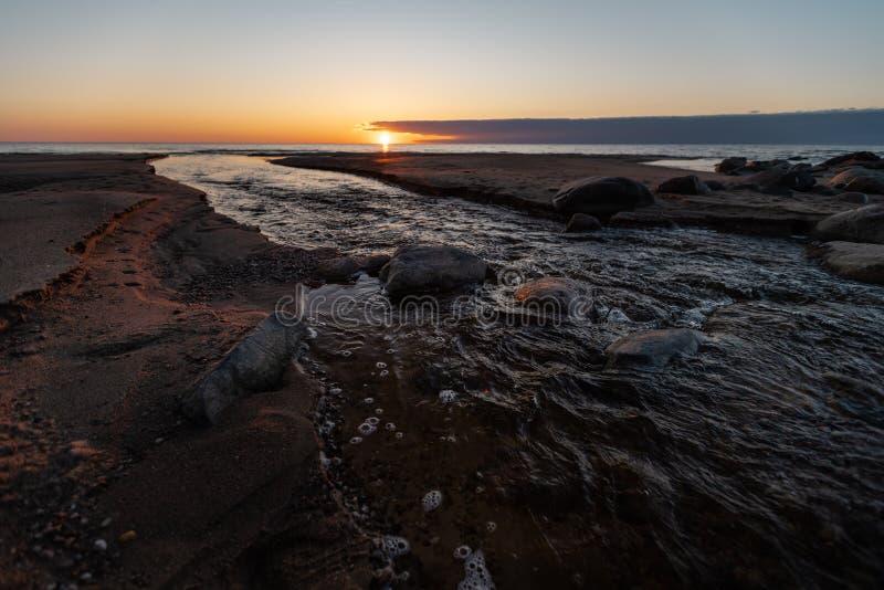Beau coucher du soleil avec le sable et l'eau de source rouges d'une rivière sortant à la mer - Veczemju Klintis, Lettonie - 13 image stock