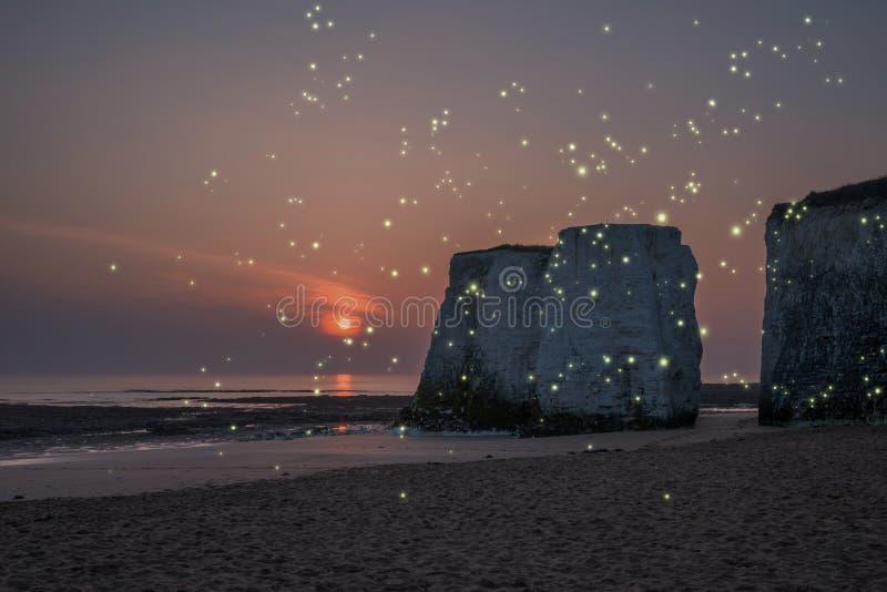 Beau coucher du soleil coloré au-dessus des piles de roche sur la plage avec le firefli photo stock
