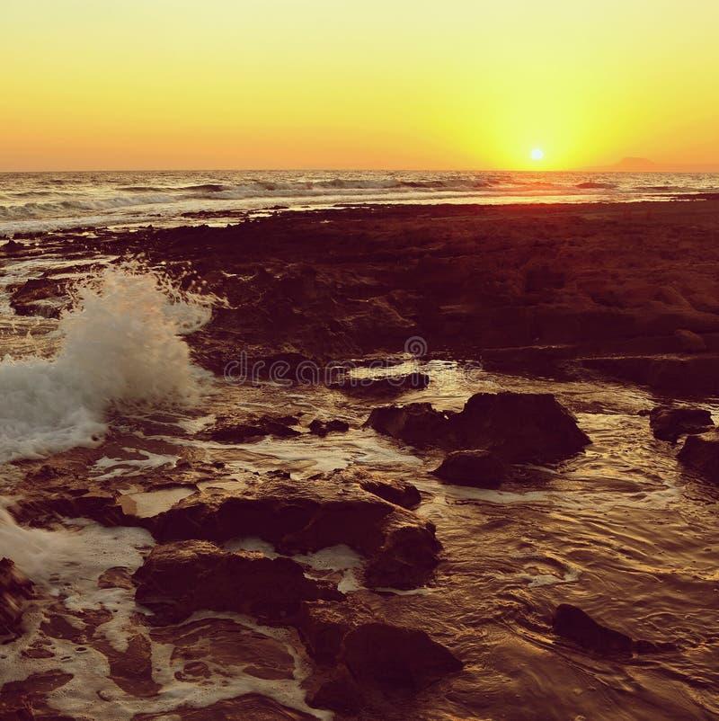 Beau coucher du soleil d'été par la mer Paysage étonnant sur la plage avec des vagues et la réflexion du soleil Fond pour des vac photographie stock