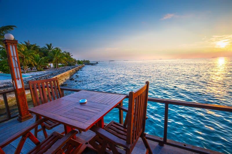 Beau coucher du soleil de restaurant sur la plage Île tropicale W photo libre de droits