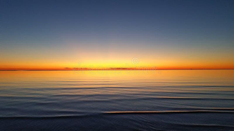 Beau coucher du soleil orange sur l'eau de mer silencieuse images libres de droits