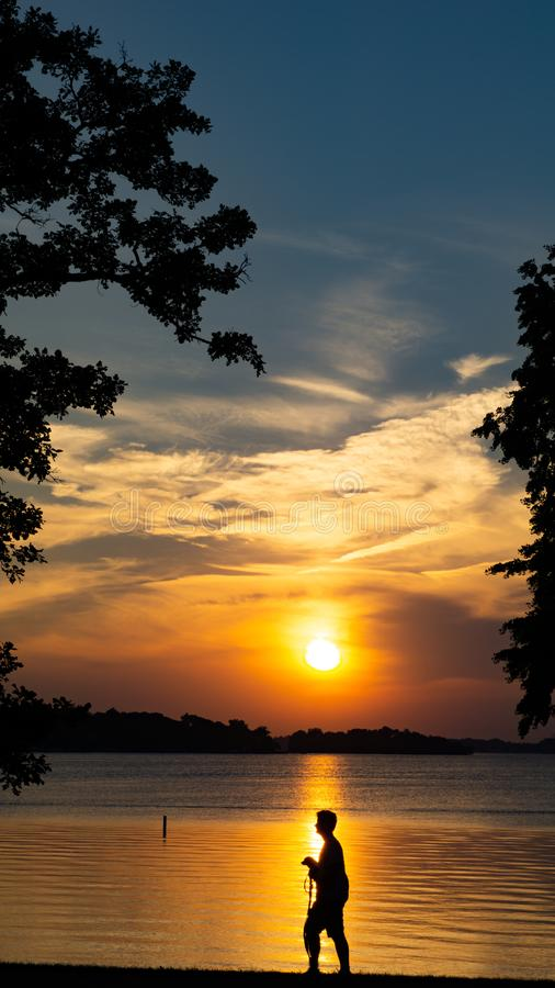 Beau coucher du soleil par le lac avec un garçon marchant sa silhouette de chien photographie stock