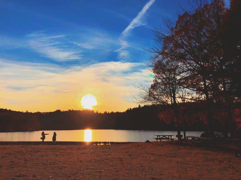 Beau coucher du soleil par le lac et la silhouette d'arbres photographie stock
