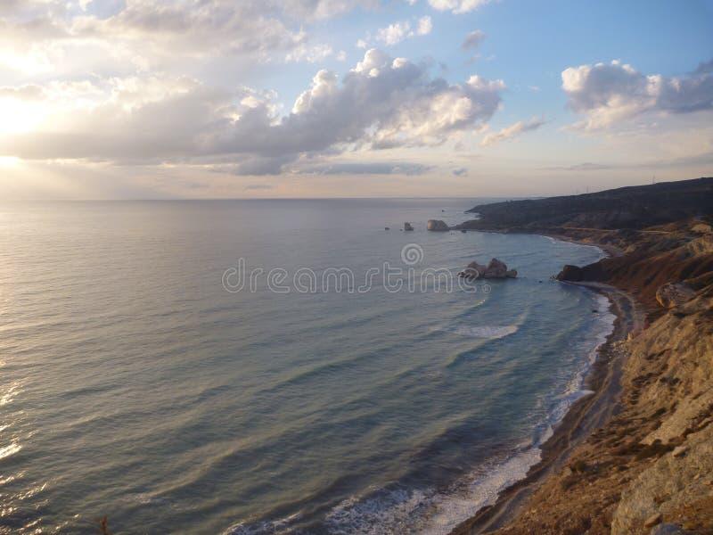 Beau coucher du soleil romantique à un bord de la mer rocheux image stock