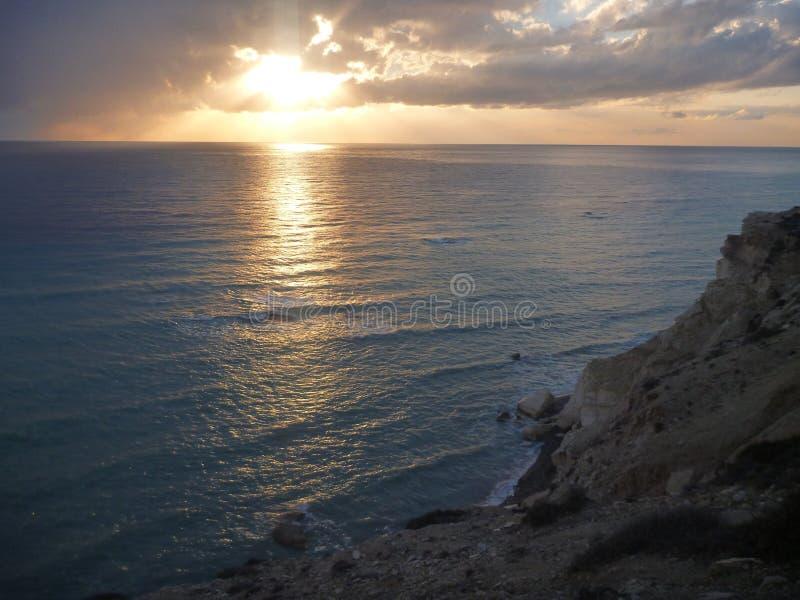 Beau coucher du soleil romantique à un bord de la mer rocheux photo stock