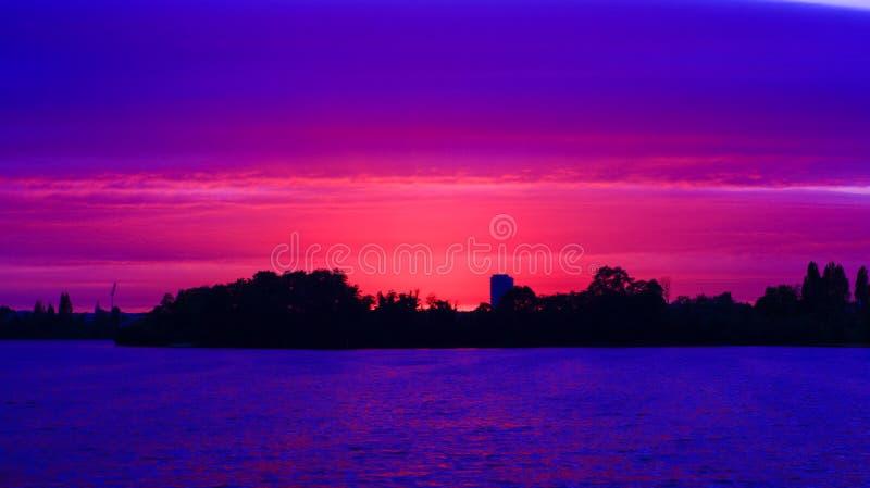 Beau coucher du soleil romantique derrière la silhouette d'une forêt dans la distance dans la campagne photographie stock