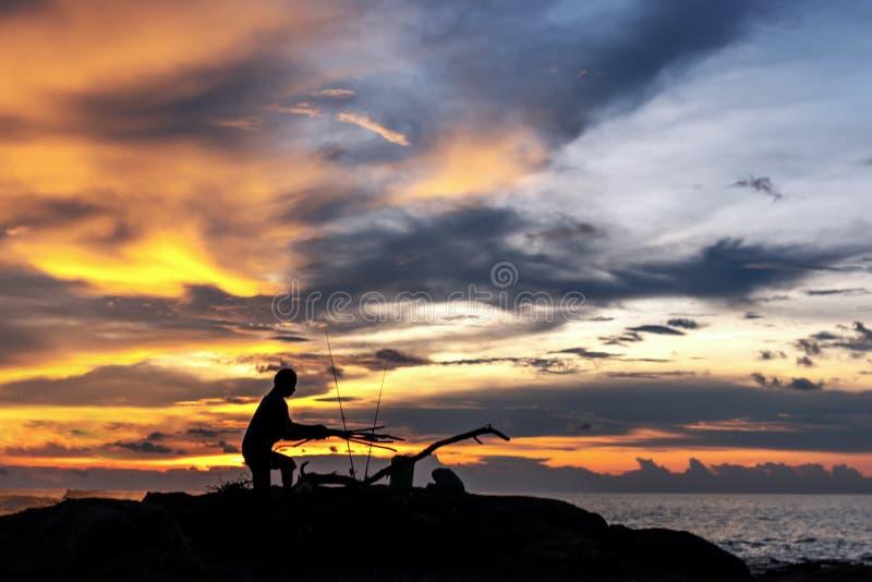 Beau coucher du soleil sur la mer l'homme, le pêcheur va faire un feu Silhouette images stock