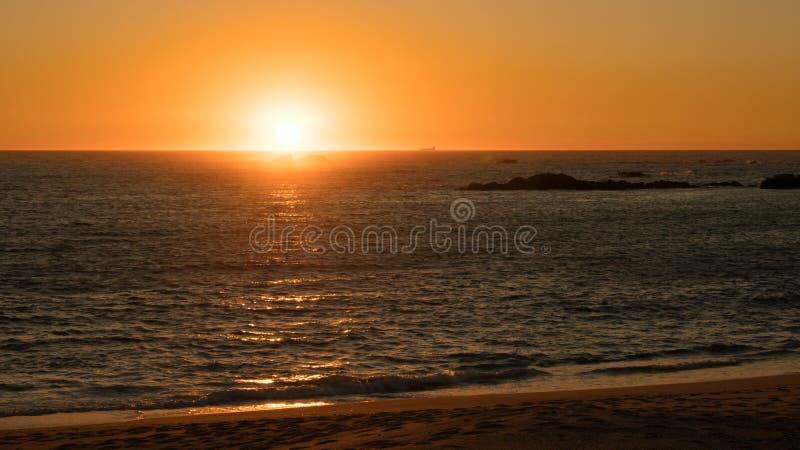 Beau coucher du soleil sur la plage au Portugal comme immersions du soleil au-dessous d'horizon image libre de droits