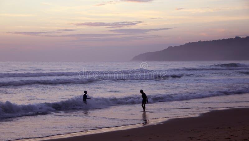 Beau coucher du soleil sur la plage de Karon Le ressac martèle le rivage Silhouettes foncées des enfants jouant dans le ressac Ph images libres de droits