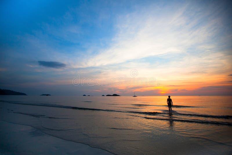 Beau coucher du soleil sur la plage de mer, silhouette de natation de filles photo stock