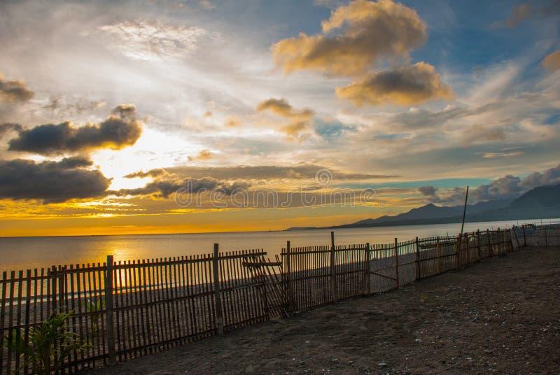 Beau coucher du soleil sur la plage La silhouette de la barrière des conseils Pandan, Panay, Philippines image libre de droits