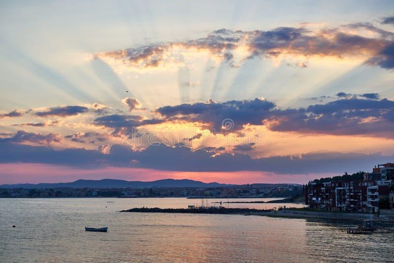 Beau coucher du soleil sur le bord de la mer avec les maisons r?sidentielles sur le rivage photos stock