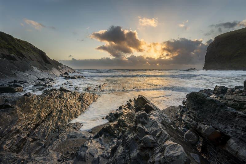 Beau coucher du soleil vibrant coloré au-dessus de plage rocheuse avec le long exp photographie stock libre de droits