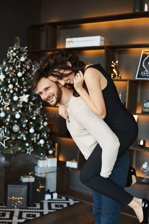 Beau couple en train de se bousculer pendant la séance de photographie du nouvel an. Jeune femme mince en tenue movale et bel hom images stock