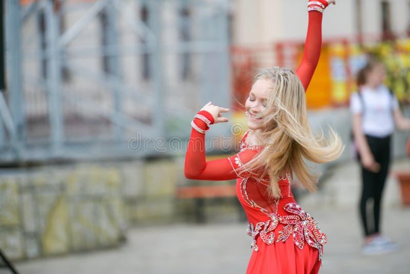 Beau danseur dans une robe rouge Belle danse de jeune fille dans une robe rouge Danse l'en public L'enfant doué fait danse photos libres de droits