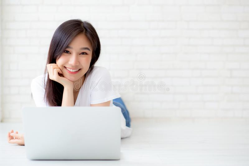 Beau de la jeune femme asiatique de portrait travaillant l'ordinateur portable en ligne se trouvant sur le fond de ciment de briq photos libres de droits