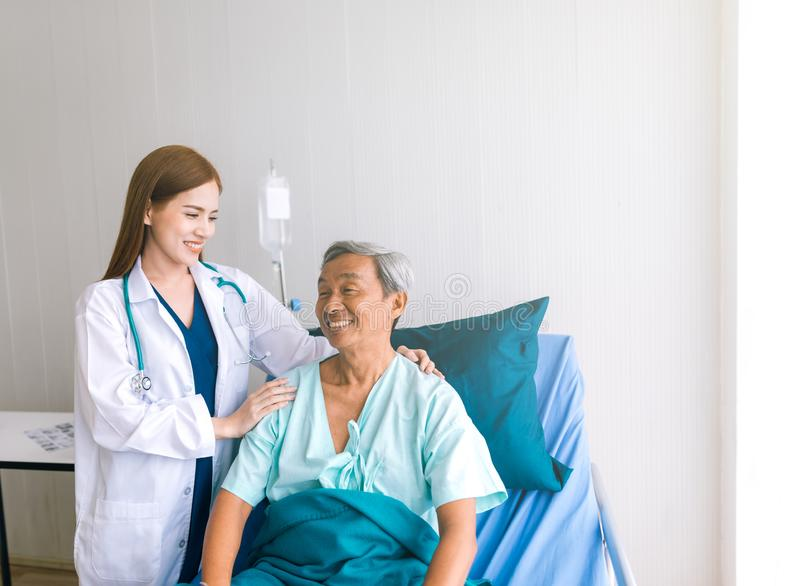 Beau docteur asiatique prenant soin de patient supérieur dans le lit d'hôpital photos libres de droits