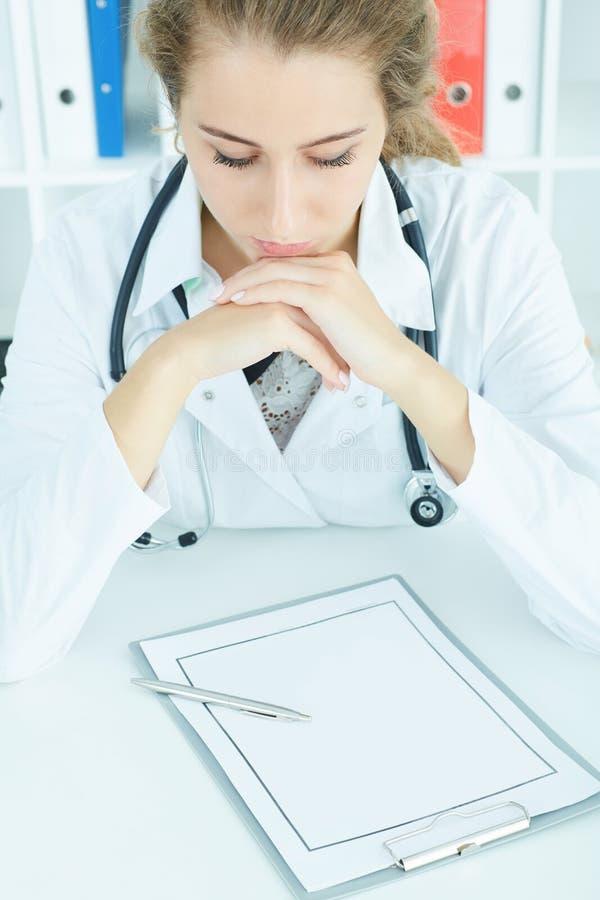 Beau docteur caucasien féminin de médecine s'asseyant à la table travaillant aux documents Concept de soins médicaux ou d'assuran image stock