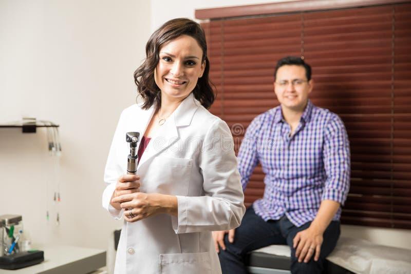 Beau docteur examinant un patient photos libres de droits