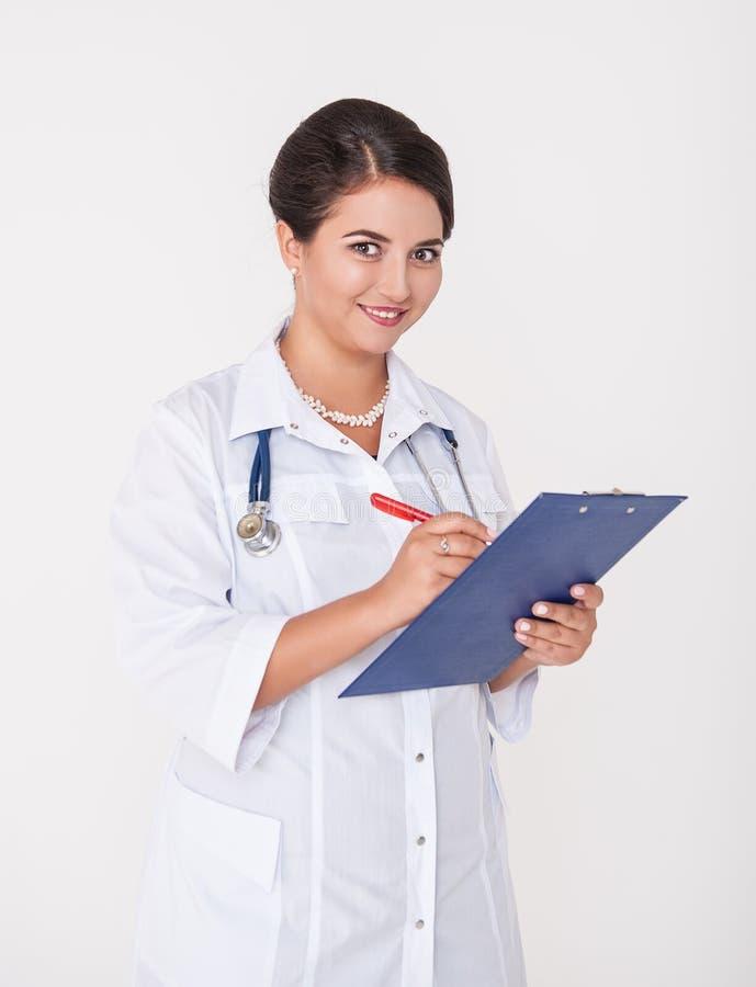 Beau docteur heureux de femme souriant avec le presse-papiers sur le blanc images stock
