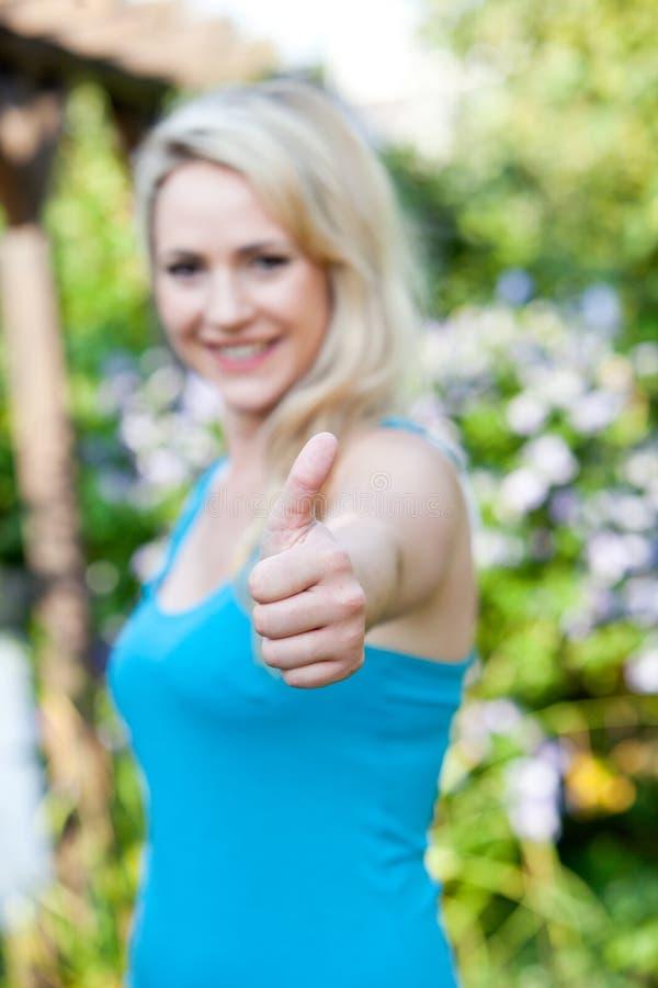 Beau donner de femme des pouces lèvent le geste photo stock