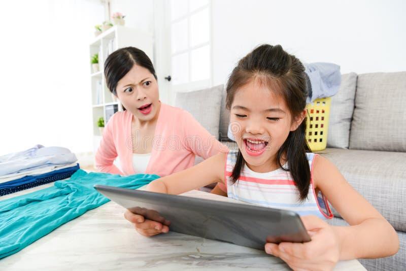 Beau enfant de petite fille à l'aide du comprimé numérique mobile photo stock