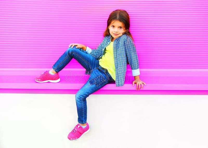 Beau enfant de petite fille posant sur la rue de ville sur le mur rose coloré images libres de droits