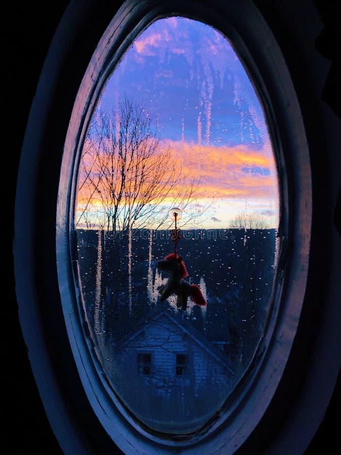 Beau et coloré coucher du soleil par la fenêtre image stock