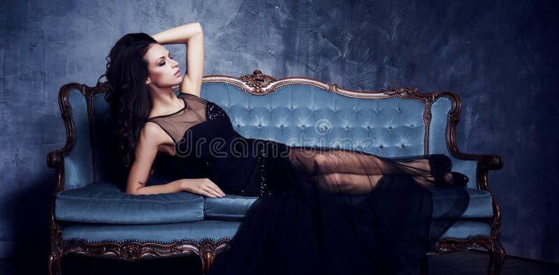Beau et jeune femme posant dans la robe noire sur le sofa bleu vi images libres de droits