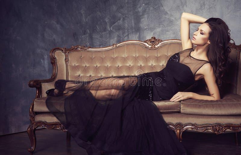 Beau et jeune femme posant dans la robe noire sur le sofa brun V image libre de droits
