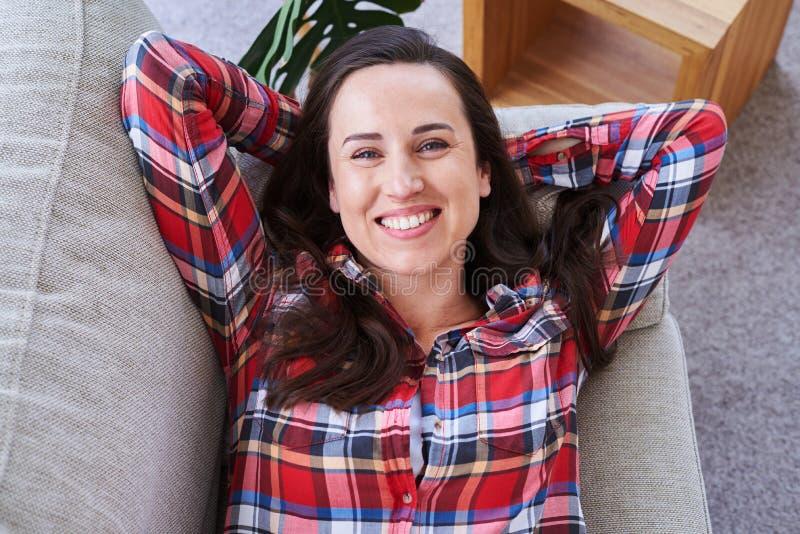 Beau femelle ayant le repos tout en se trouvant sur le sofa images libres de droits