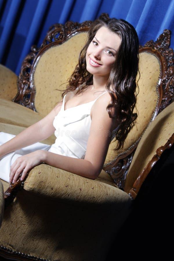 Beau femme élégant s'asseyant dans le fauteuil photographie stock libre de droits
