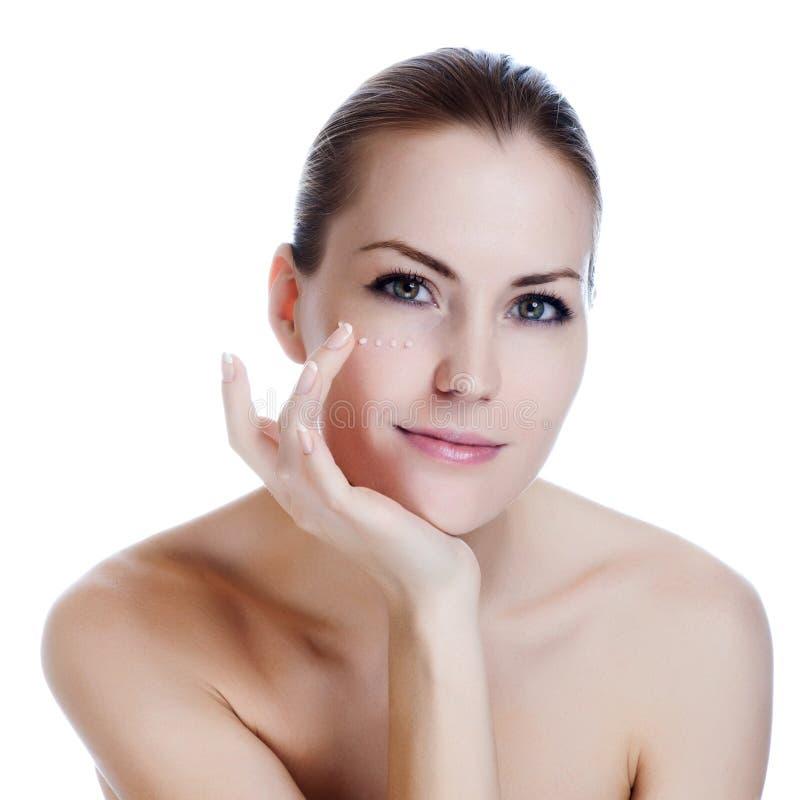 Beau femme appliquant la crème sur la peau près des yeux photographie stock