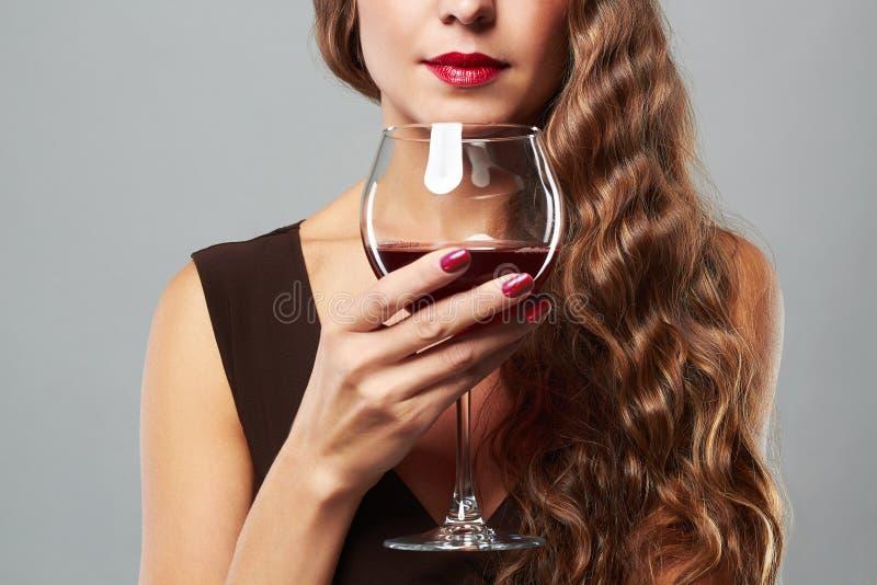Beau femme avec le vin rouge en verre Coiffure bouclée photographie stock libre de droits