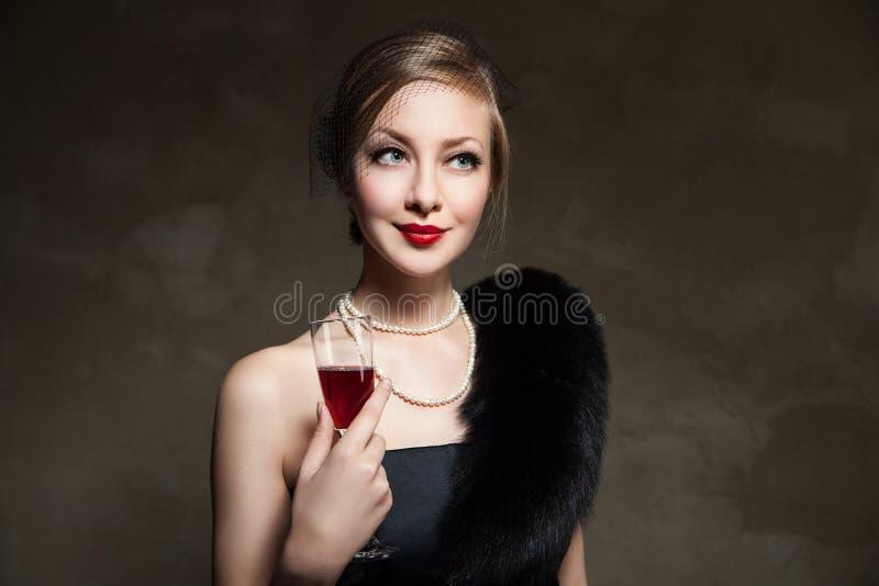 Beau femme avec le vin rouge en verre Rétro type image stock