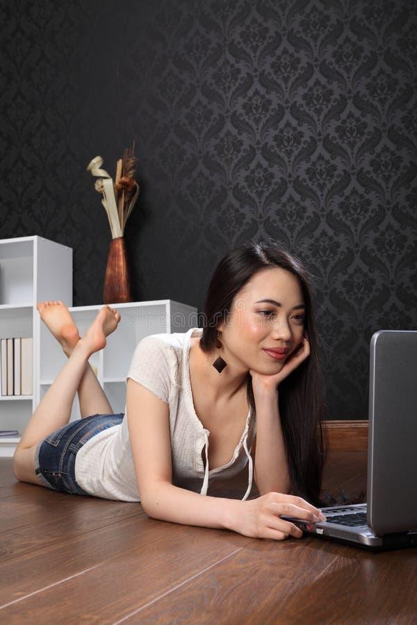 Beau femme chinois à la maison surfant l'Internet photographie stock libre de droits