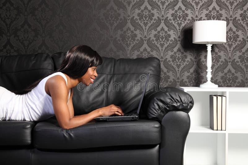 Beau femme d'afro-américain à la maison avec le PC image libre de droits
