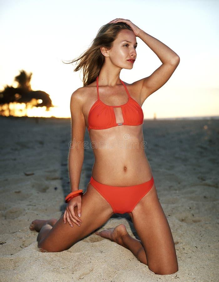 Beau femme dans le bikini rouge, coucher du soleil sur la plage image libre de droits