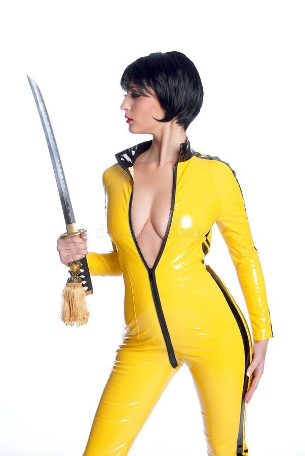 Beau femme dans le procès de saut jaune de latex photos stock