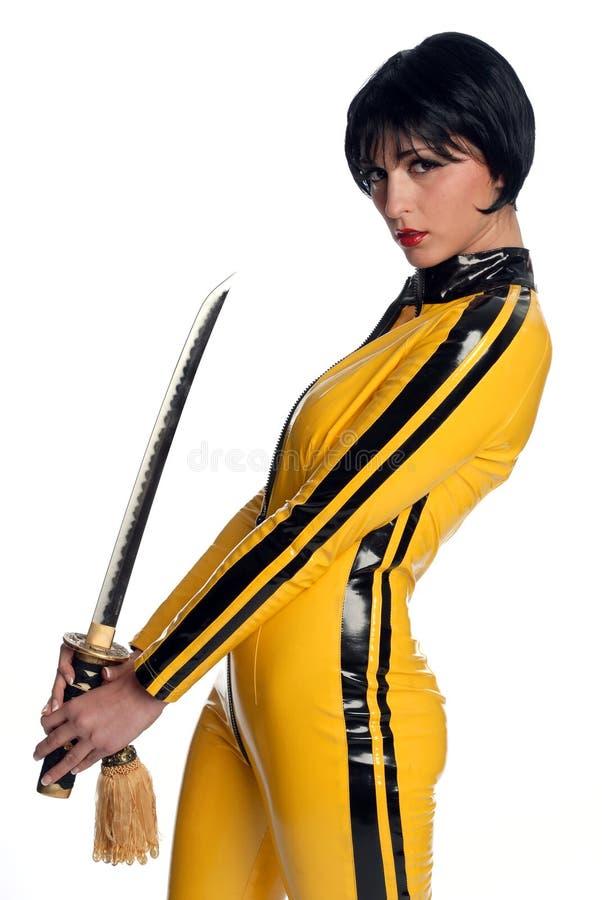 Beau femme dans le procès de saut jaune de latex photographie stock